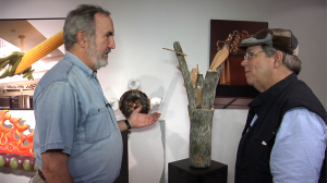 "Craig Nutt (Left) shows Charles Brock his ""Make a Tree from a Chair"" piece."